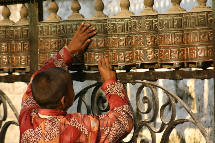 a child at a prayer wheel, feeling the encryption